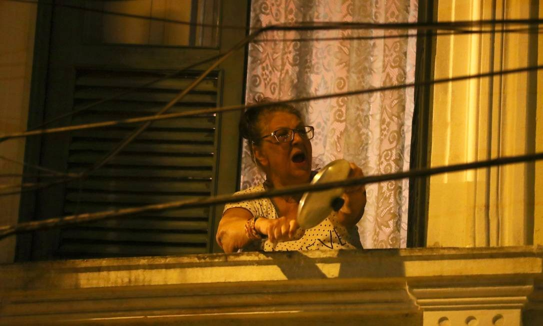 Uma mulher bate panela em sua janela enquanto protesta contra o presidente do Brasil, Jair Bolsonaro, durante quarentena no Rio de Janeiro Foto: PILAR OLIVARES / REUTERS