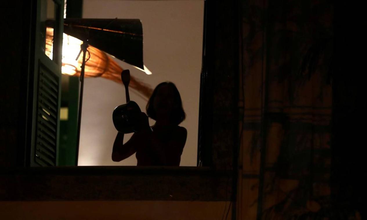 Mulher bate um pote na janela de seu apartamento no Rio de Janeiro durante pronunciamento de Bolsonaro Foto: PILAR OLIVARES / REUTERS