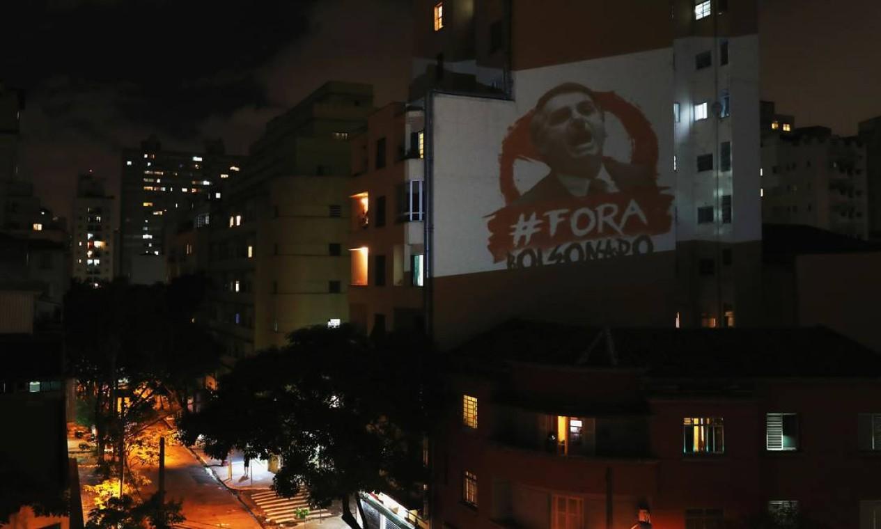 """Imagem que descreve o presidente do Brasil, Jair Bolsonaro, e a frase """"fora, Bolsonaro"""" é projetada durante a declaração do presidente na TV sobre o surto da Covid-19, em São Paulo Foto: AMANDA PEROBELLI / REUTERS"""