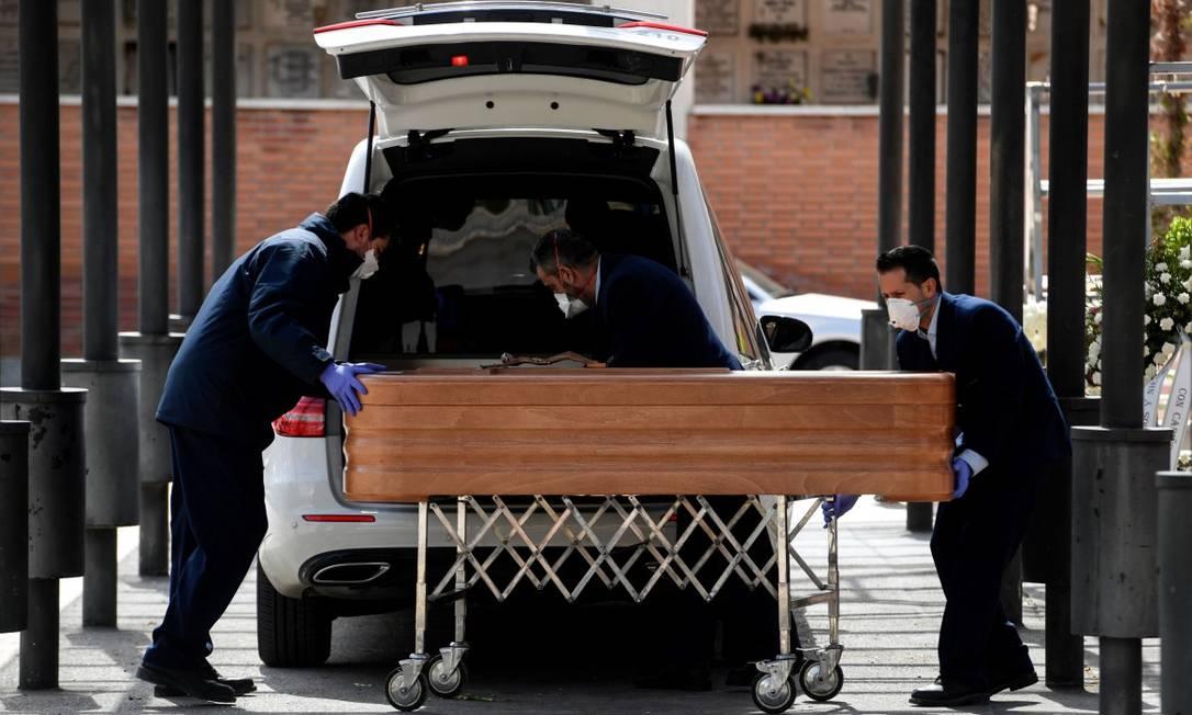 Funcionários de uma funerária levam caixão de vítima da Covid-19 para crematório Foto: OSCAR DEL POZO / AFP