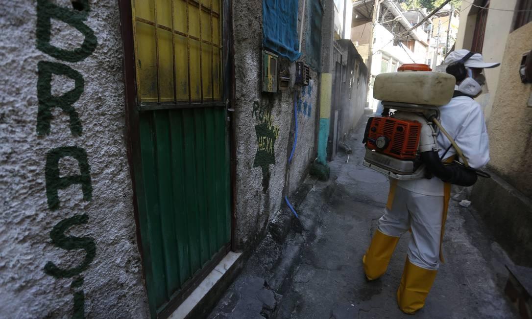 Sanitização acontece em becos e vielas, além das ruas principais da comunidade Foto: Fabiano Rocha / Agência O Globo