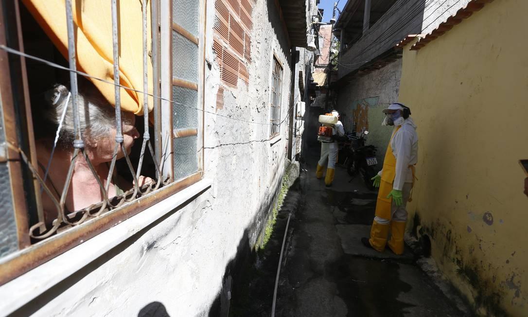 Idosa observa da janela trabalho de equipe de sanitização em viela da Vila Ipiranga, no Fonseca, Niterói Foto: Fabiano Rocha / Agência O Globo