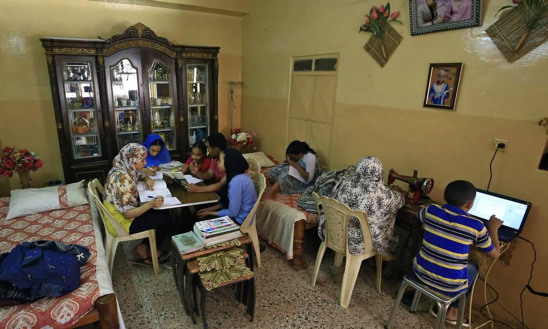 Família estuda e trabalha junta, no mesmo cômodo da casa, em Cartum, capital do Sudão. País do norte da África, adotou o fechamento de escolas e universidades como prevenção ao novo coronavírus Foto: ASHRAF SHAZLY / AFP