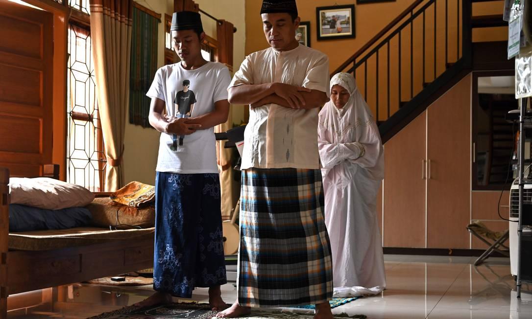 Família de Tangerang, na Indonésia, realiza as orações islâmicas do meio-dia em casa. Governo pediu aos muçulmanos que adotem distanciamento social, como medida preventiva contra a propagação. Até a sexta-feira passada, comunidade islâmica ainda lotavam mesquitas para orações obrigatórias Foto: ADEK BERRY / AFP