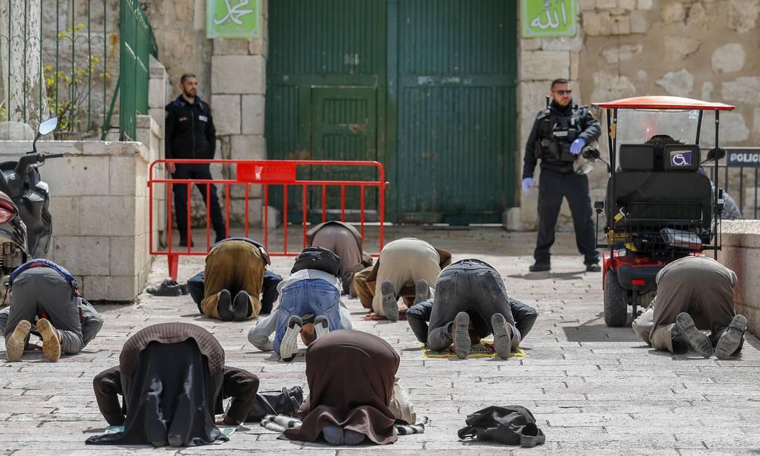 Muçulmanos palestinos oram diante de forças de segurança israelenses, próximno ao portão fechado do complexo da mesquita Aqsa. A autoridade religiosa Jordan Waqf, que administra o local, determinou o fechamento dos portões como parte de medidas preventivas contra a propagação do novo coronavírus Foto: AHMAD GHARABLI / AFP