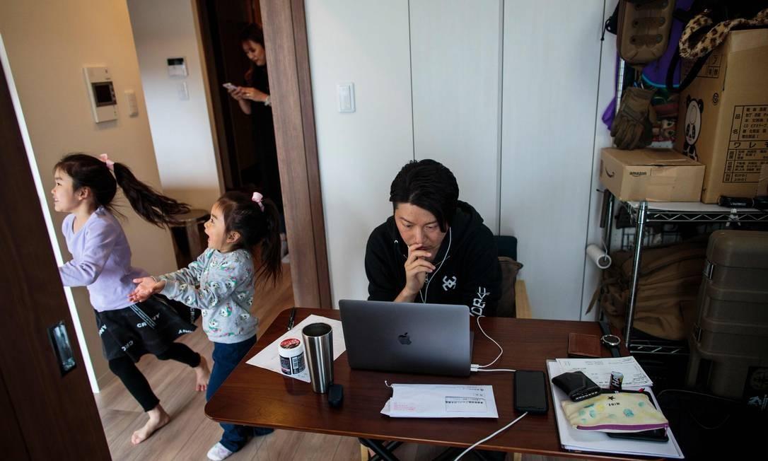 Em Tóquio, funcionário de startup adotou trabalho remoto para contribuir com o distanciamento social, como medida de combate à disseminação do novo coronavírus. As duas filhas e a esposa também mantém confinamento Foto: BEHROUZ MEHRI / AFP