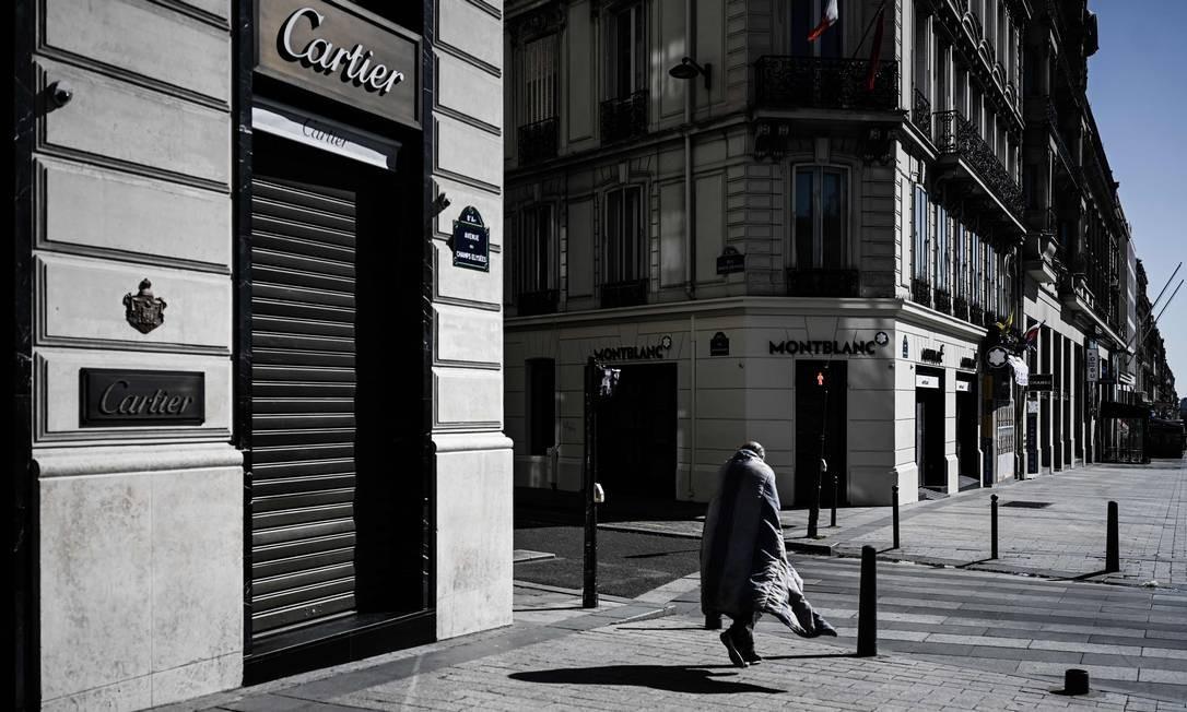 Sem-teto anda pela Champs Elysée, avenida mais icônica e uma das mais movimentadas de Paris, durante o estrito bloqueio na França para impedir a propagação do novo coronavírus Foto: PHILIPPE LOPEZ / AFP