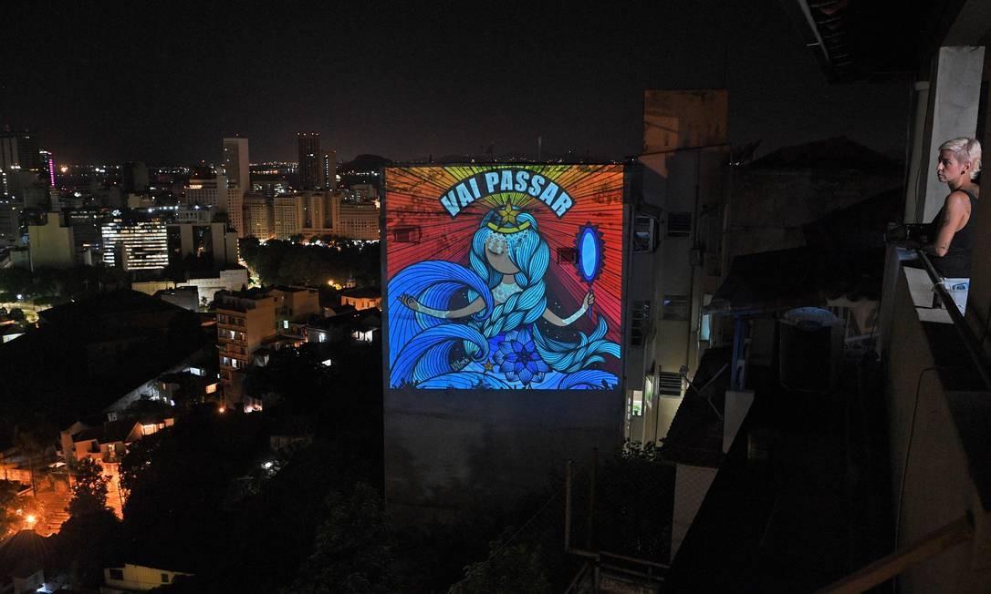 Grafiteira Rafamon (à direita) projeta seu trabalho artístico com uma mensagem de otimismo em um prédio perto de sua casa no Rio de Janeiro, depois que ela decidiu se isolar como medida preventiva contra o novo coronavírus Foto: CARL DE SOUZA / AFP