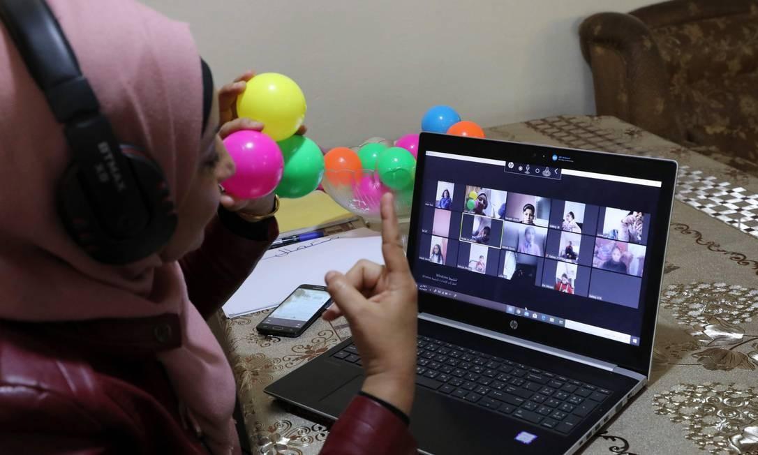 Pofessora palestina apresenta aula on-line de sua casa na vila de Dura, perto de Hebron, na Cisjordânia, depois que as escolas foram fechadas como medida preventiva contra a propagação da Covid-19 Foto: HAZEM BADER / AFP