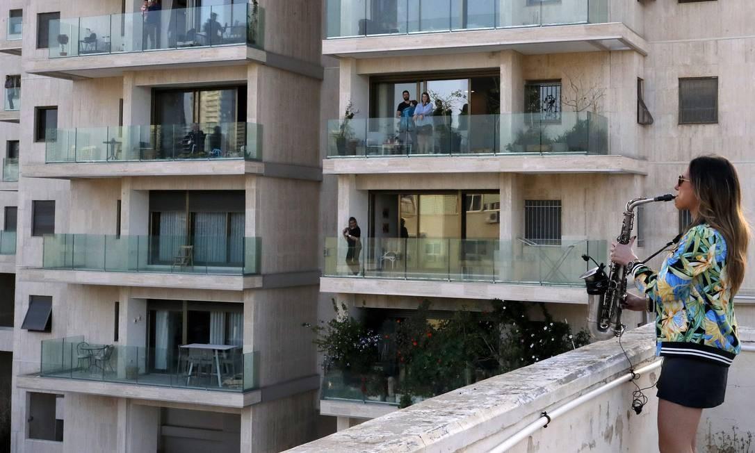 Saxofonista Yarden Klayman se apresenta para vizinhança de terraço na praça Basel, em Tel Aviv, Israel, depois que seu show foi cancelado devido ao novo coronavírus Foto: JACK GUEZ / AFP