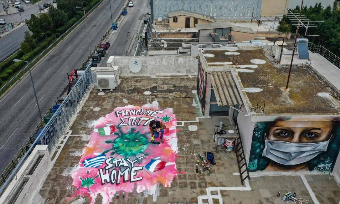 """Artista de rua de 16 anos pinta grafite no terraço do prédio onde vive, em Atenas. A ilustração traz a mensagem: """"fique em casa"""", escrita em inglês e em grego Foto: ARIS MESSINIS / AFP"""