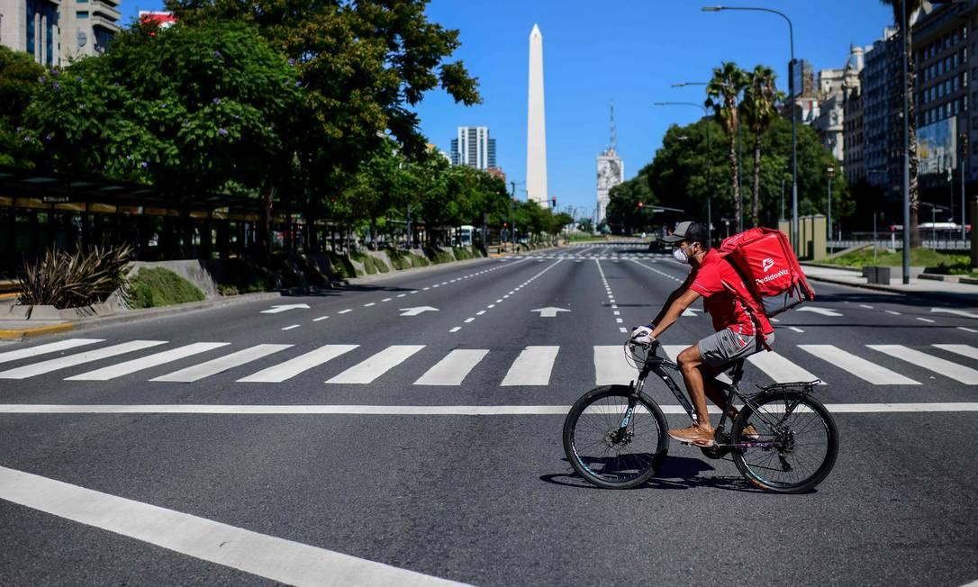 Entregador de bicicleta pedala em ao longo da Avenida 9 de Julho, uma das mais importantes de Buenos Aires, deserta. A demanda dos serviços de entrega dispararam na capital argentina, à medida governo adota meiddas que restringe a circulação de pessoas Foto: RONALDO SCHEMIDT / AFP