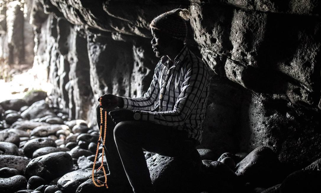 Membro da comunidade Layenne ora na sagrada Caverna das Almadies, onde a próxima peregrinação anual da comunidade foi cancelada devido ao novo coronavírus, em Dacar, capital do Senegal Foto: JOHN WESSELS / AFP
