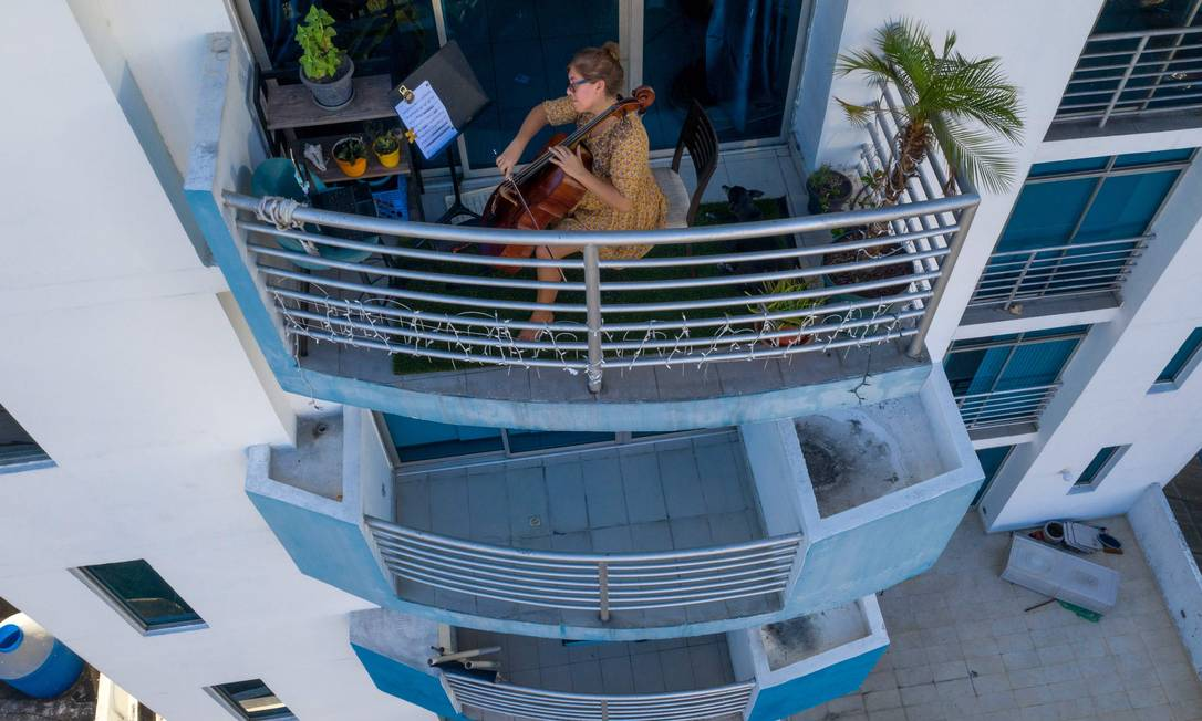 Violoncelista uruguaia Karina Nunez toca na varanda de seu apartamento, na Cidade do Panamá, durante o isolamento obrigatório Foto: LUIS ACOSTA / AFP