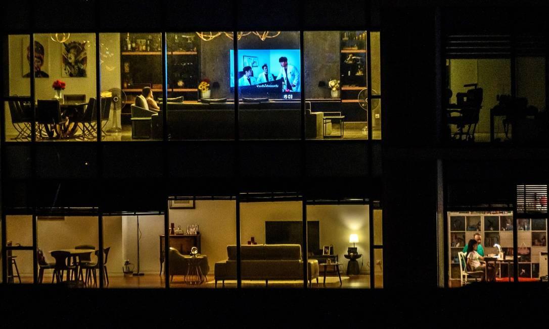 Todo mundo em casa. Apartamentos em Bangcoc são visto completamente iluminados, enquanto Thailândia enfrenta a pandemia com isolamento social Foto: MLADEN ANTONOV / AFP