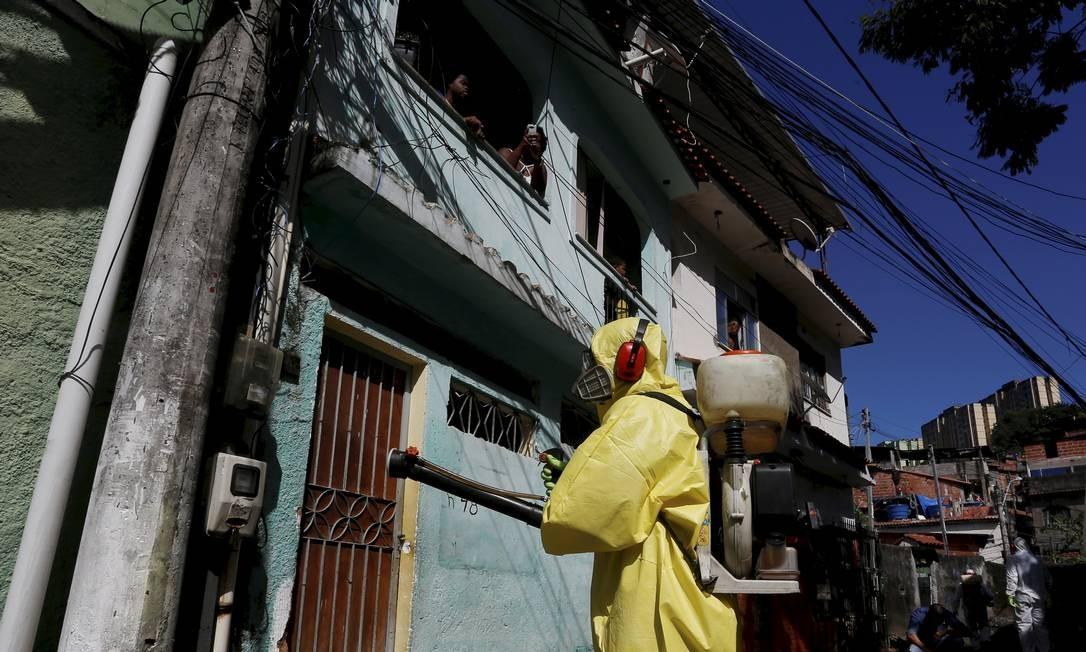 Serviço de sanitização contra o novo coronavírus chamou atenção dos moradores, que observaram o trabalho de dentro de casa Foto: Fabiano Rocha / Agência O Globo