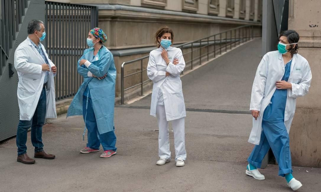 Profisisonais de saúde do lado de fora de um hospital, em Barcelona, na Espanha Foto: The New York Times