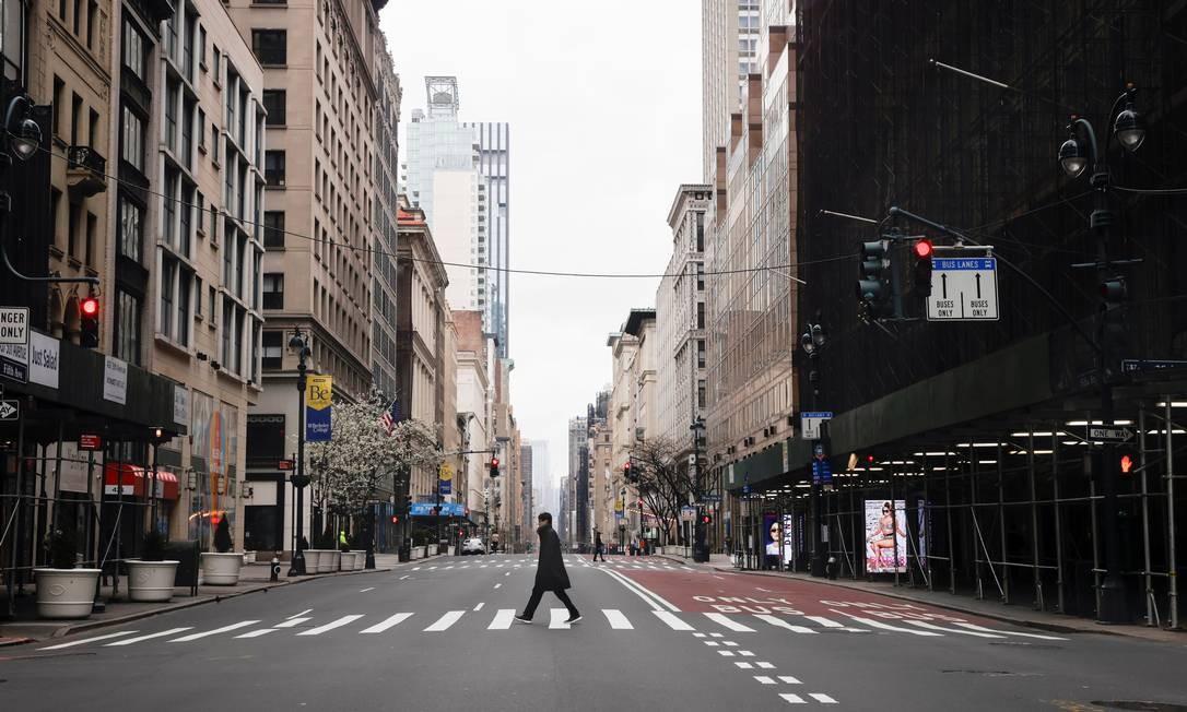 Homem atravessa uma deserta 5ª avenida em Manhattan, nesta quinta-feira. Cidade registra quase 18 mil casos de coronavírus Foto: MIKE SEGAR / REUTERS