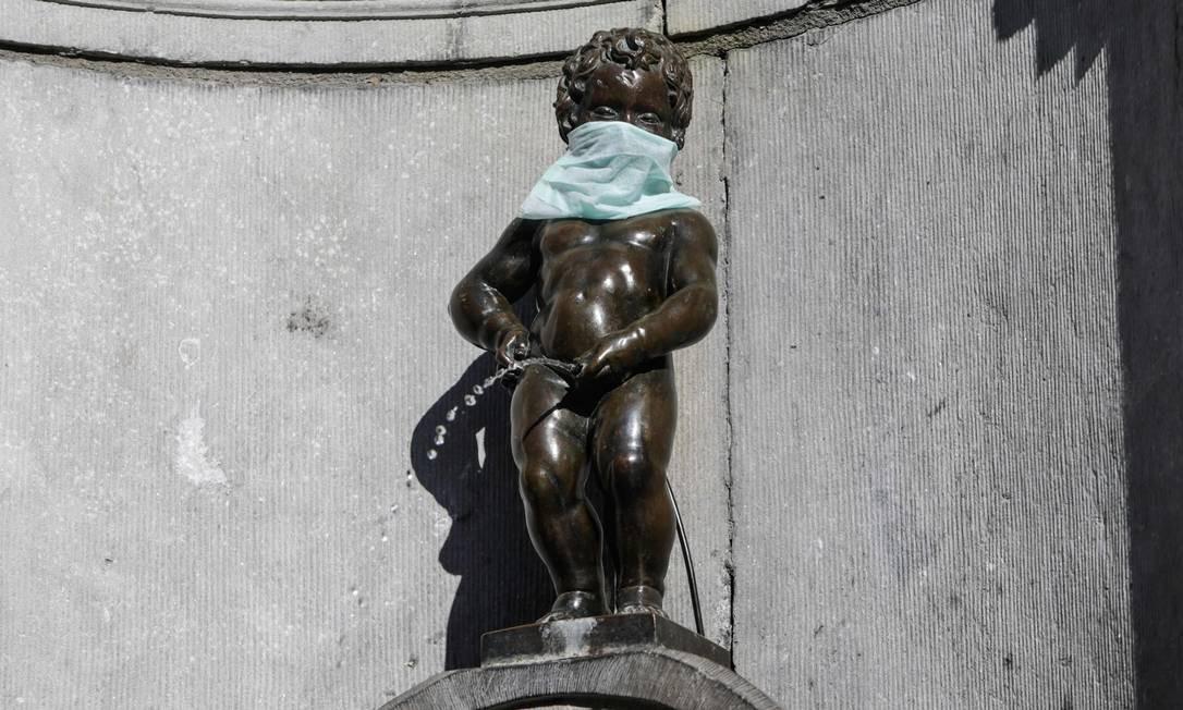 Estátua de Manneken-Pis, com máscara protetora, em Bruxelas, Bélgica Foto: ARIS OIKONOMOU / AFP