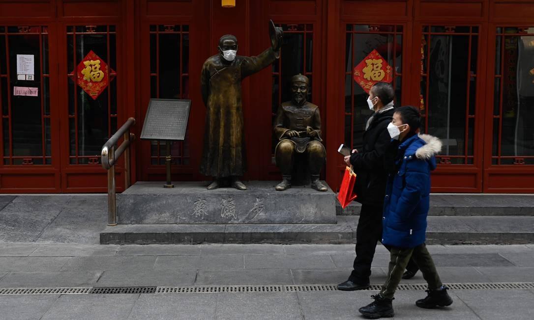 Pessoas usam máscaras enquanto passam em frente a uma estátua também com máscara em uma rua de Pequim, na China Foto: STR / AFP