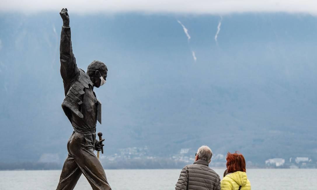 Estátua do falecido cantor Freddie Mercury, adornada com uma máscara protetora, nas margens do Lago Genebra, em Montreux Foto: FABRICE COFFRINI / AFP