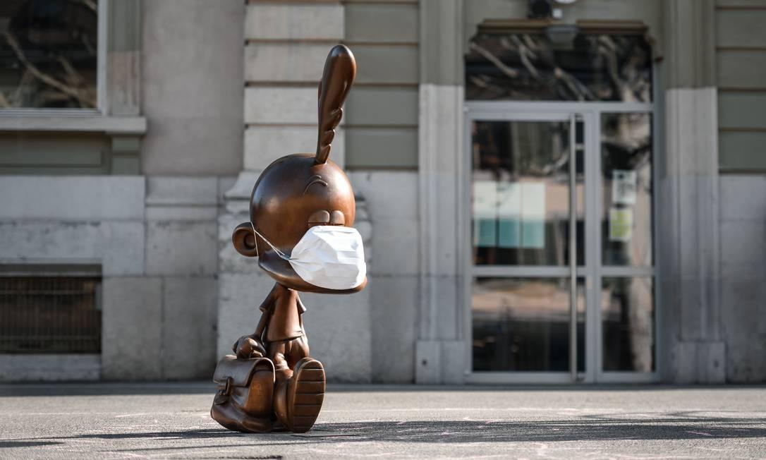 Uma estátua de bronze representando o personagem de desenho animado Titeuf, o menino de 8 anos com um capuz loiro criado pelo cartunista suíço Zep, também recebeu uma máscara protetora no pátio da escola fechada de Carouge, perto de Genebra, na Suíça Foto: FABRICE COFFRINI / AFP