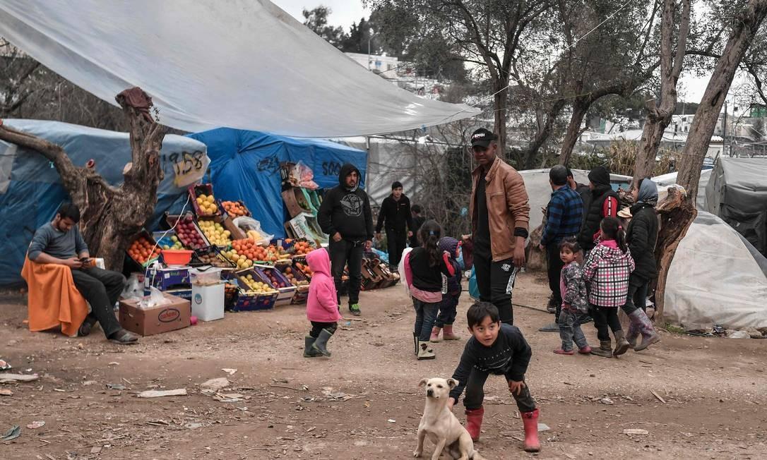 Criança brinca com cachorro no campo de refugiados superlotado de Moria, na ilha de Lesbos, na Grécia Foto: LOUISA GOULIAMAKI / AFP/07-03-2020