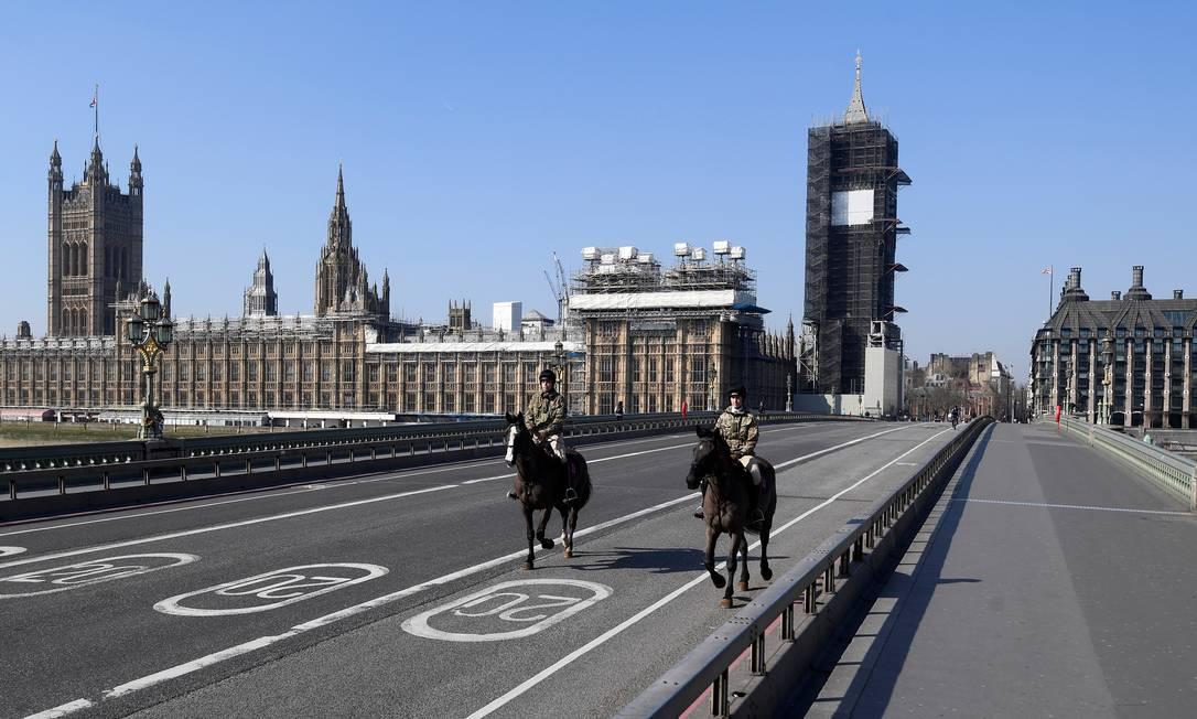 Membros da cavalaria do Parlamento inglês passam pela ponte de Westminster, completamente vazia, após as medidas de restrição em Londres por causa da disseminação da Covid-19, doença causaada pelo novo coronavírus Foto: Toby Melville / Reuters