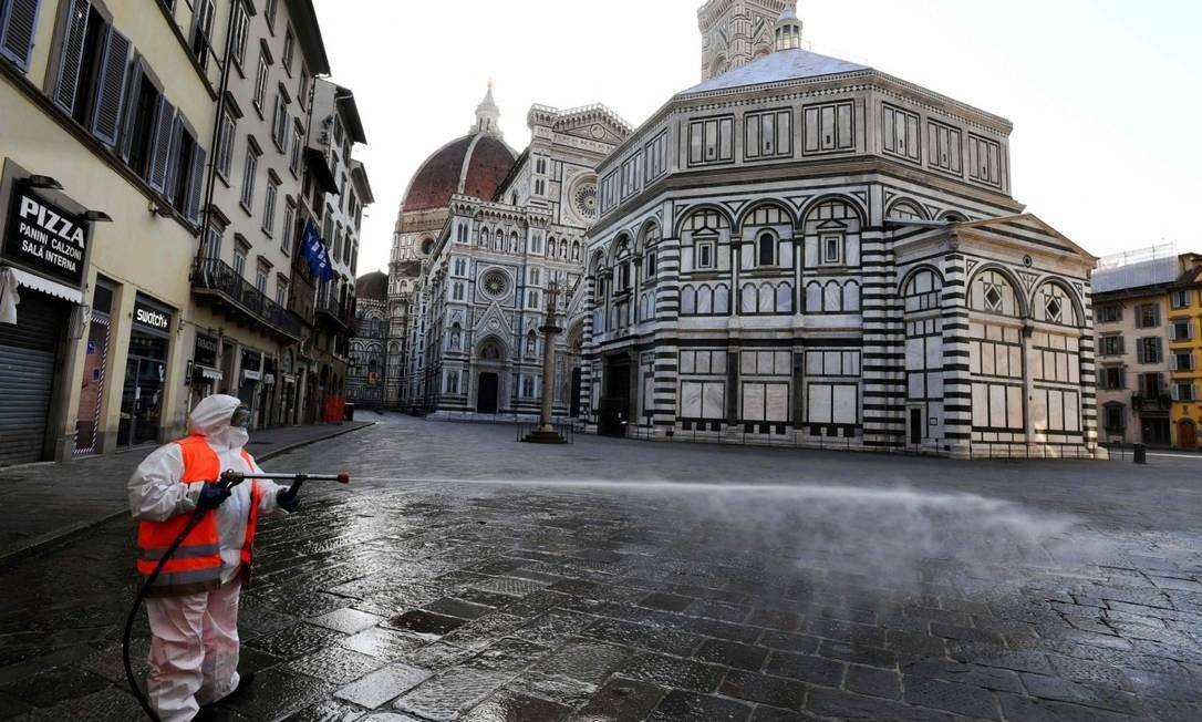 Homem desinfecta rua em Florença, na Itália, sob quarentena Foto: CARLO BRESSAN / AFP
