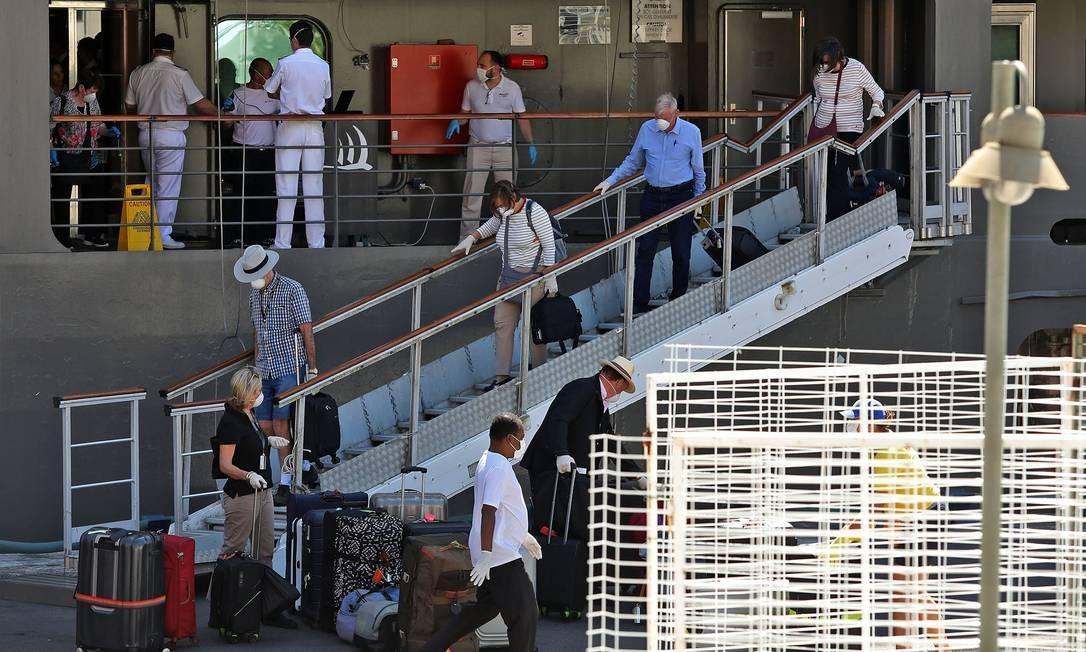 Cerca de 30 passageiros do cruzeiro francês Le Boreal desembarcaram no Porto do Rio usando luvas e máscaras na manhã desta quinta-feira após 4 dias em alto mar Foto: Fábio Motta / Agência O Globo