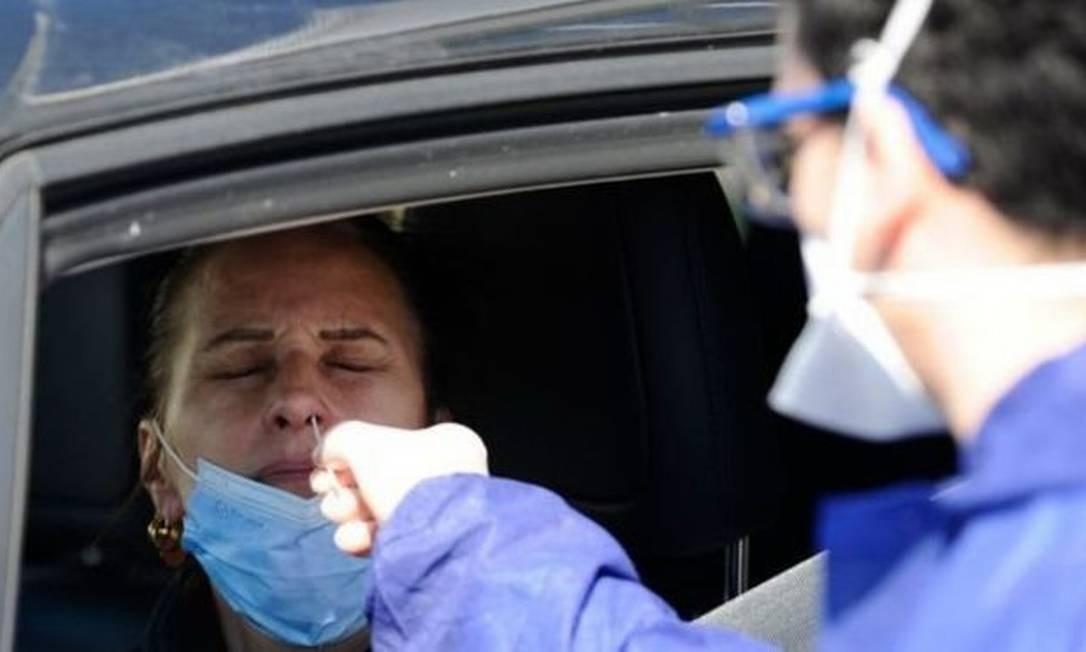 Agente sanitário coleta amostra de motorista na França para testar presença do novo coronavírus Foto: AFP