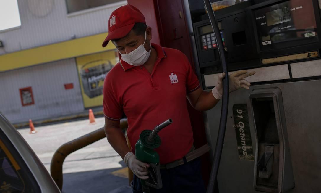 Funcionário de um posto de gasolina na Venezuela usando máscara e luvas. No país, a venda de gasolina está permitida apenas para alguns grupos por causa do novo coronavírus Foto: Cristian Hernandez / AFP