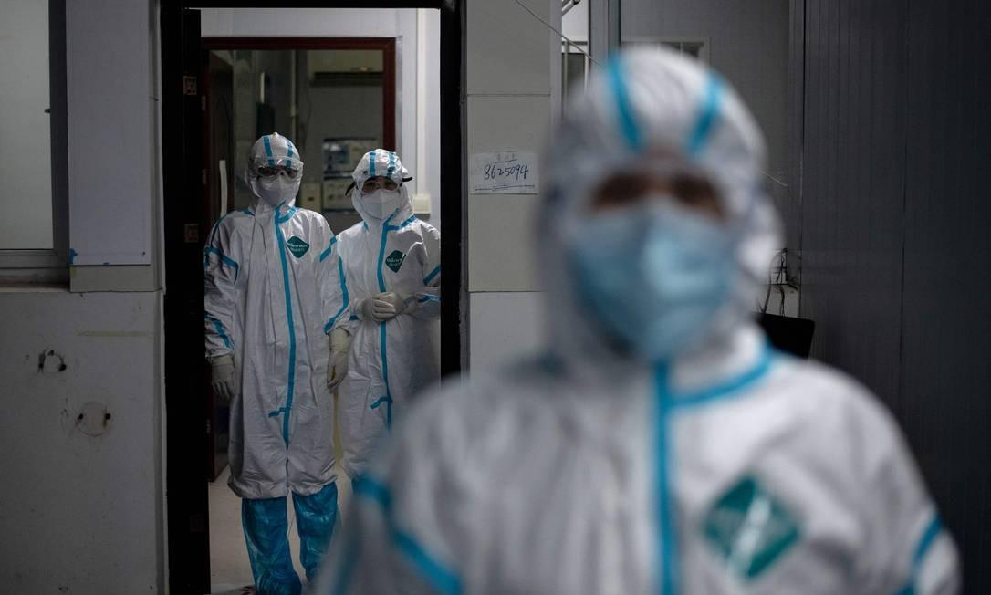 Médicos usam roupas de prevenção à Covid-19 para trabalhar em um hospital de Hubei, na China Foto: NOEL CELIS / AFP/26-03-2020