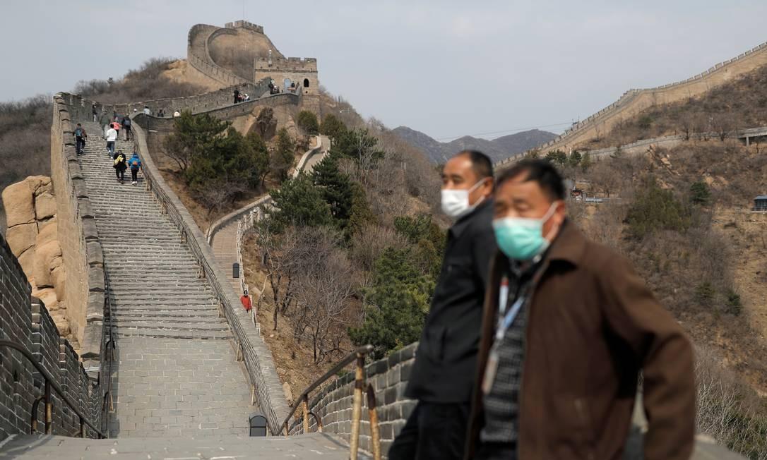 Homens de máscara no trecho da Grande Muralha da China reaberto aos turistas Foto: Thomas Peter / Reuters