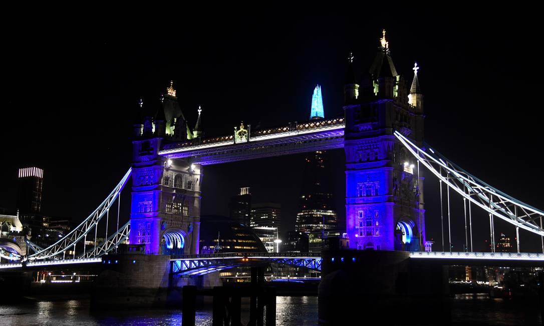 Vista geral da Tower Bridge e do Shard iluminados de azul em apoio ao Sistema Nacional de Saúde britânico na luta contra a Covid-19 Foto: TOBY MELVILLE / REUTERS/26-03-2020