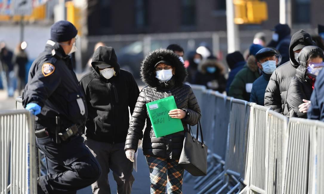 Pessoas saem depois que foram testadas para o coronavírus, no Elmhurst Hospital Center, no distrito de Queens, Nova York. Elmhurst relatou 13 pacientes com Covid -19 que morreram no hospital em um período de 24 horas, de acordo com as autoridades, em 25 de março Foto: ANGELA WEISS / AFP