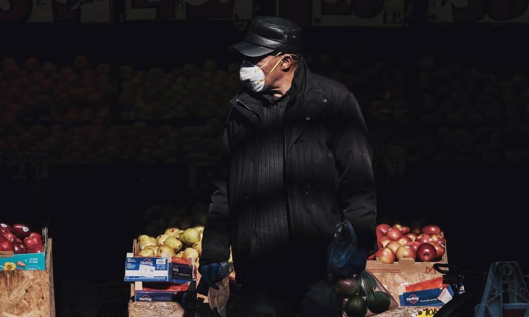 Um homem usa uma máscara em uma loja de frutas no Brooklyn, em Nova York Foto: STEPHEN YANG / REUTERS