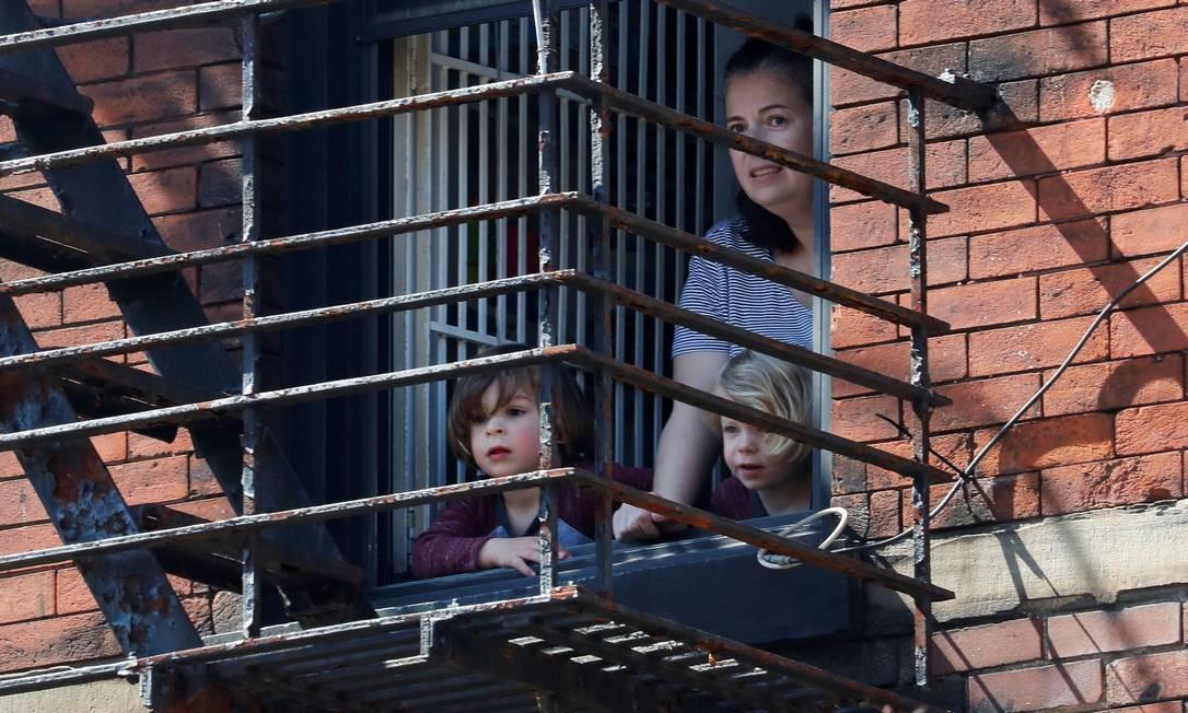 Mulher e crianças olham pela janela de um apartamento em Greenwich Village, em Manhattan, durante isolamento social decretado peo governo Foto: MIKE SEGAR / REUTERS