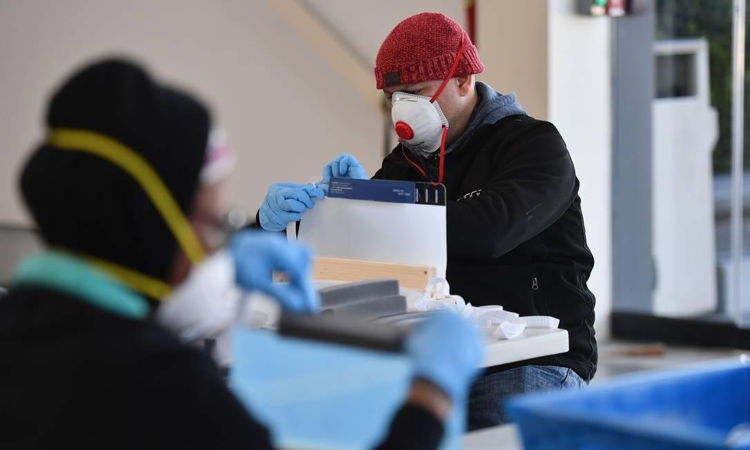 Pessoas trabalham no Brooklyn Navy Yard, onde empresas industriais locais começaram a fabricar Equipamentos de Proteção Individual (EPI) como protetores faciais para abastecer os trabalhadores e hospitais da cidade Foto: ANGELA WEISS / AFP