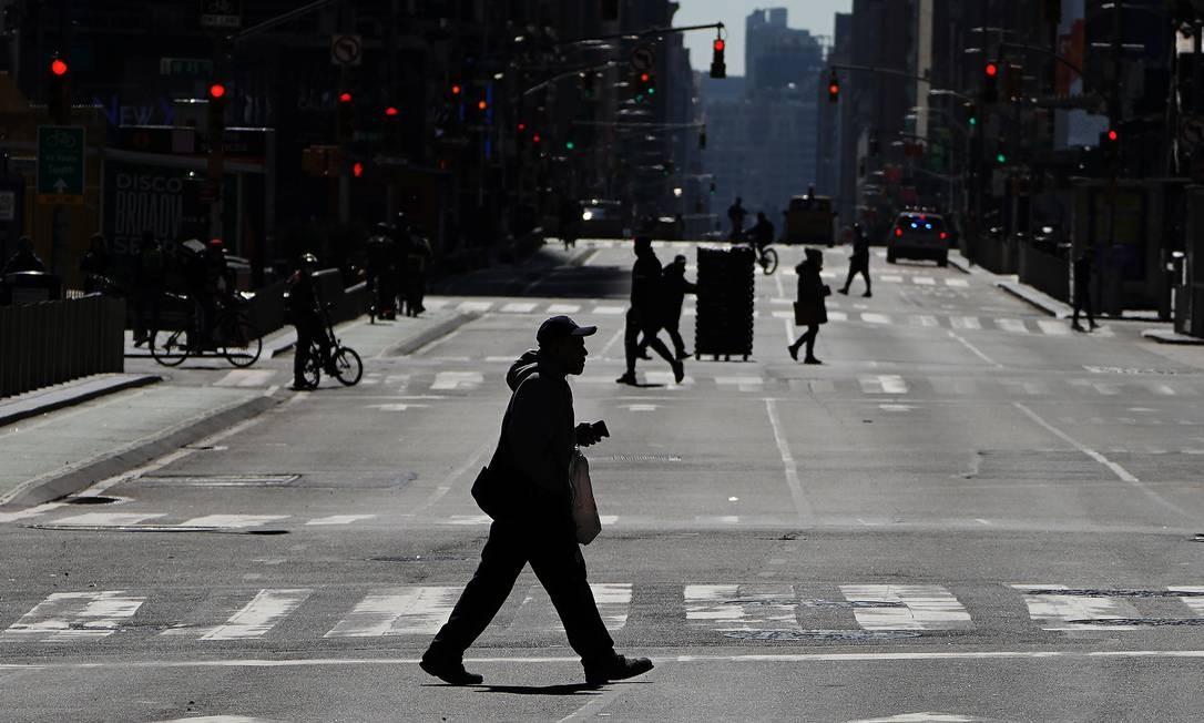 Pessoas atravessam uma Sétima Avenida deserta em Times Square, em Manhattan. Em todo o país, as escolas, empresas e locais de trabalho foram fechados ou estão restringindo o horário de funcionamento, enquanto as autoridades de saúde tentam retardar a propagação da Covid-19. Foto: CARLO ALLEGRI / REUTERS