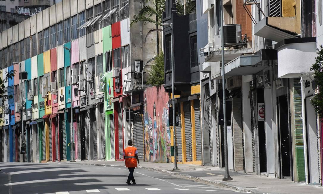 Homem caminha em rua comercial no centro de São Paulo, cidade que ordenou uma quarentena na terça-feira Foto: NELSON ALMEIDA / AFP