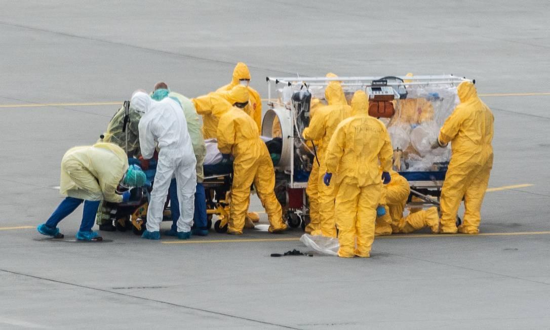 Paciente infectado com o novo coronavírus é levado por médicos para tratamento em Dresden, no leste da Alemanha Foto: ROBERT MICHAEL/AFP