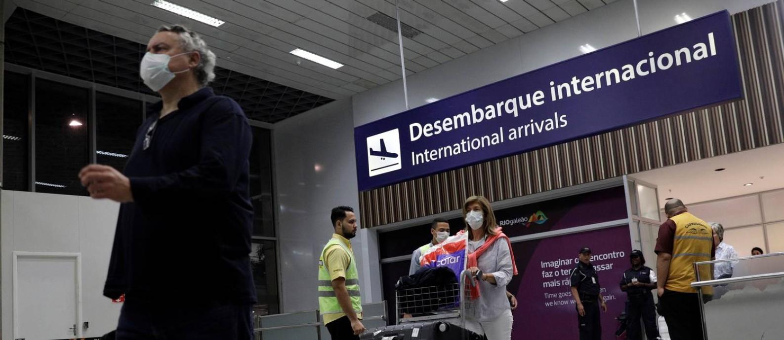 Passageiros desembarcam no Aeroporto Internacional do Galeão, no Rio, usando máscaras. Temor do coronavírus provocou queda brusca nas viagens de avião Foto: Ricardo Moraes / Reuters