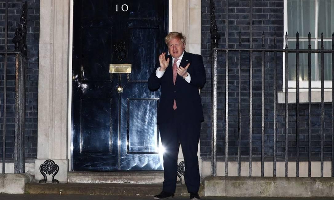 Premier Boris Johnson aplaude médicos no exterior da residência do governo britânico, na rua Downing Foto: HANNAH MCKAY / REUTERS