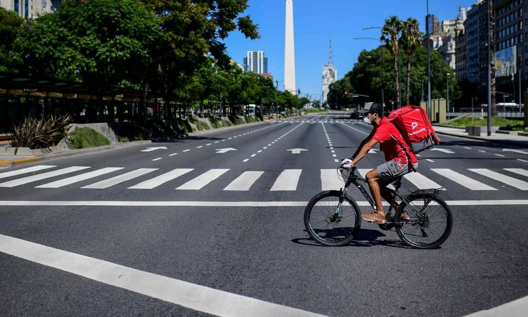 Entregador passa pela Avenida 9 de Julho, em Buenos Aires durante isolamento Foto: RONALDO SCHEMIDT / AFP