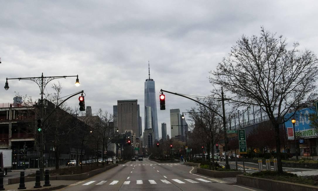 O World Trade Center é visto ao longo da West Street, na cidade de Nova York. Em todo os EUA, escolas, empresas e locais de trabalho foram fechados ou estão restringindo o horário de funcionamento Foto: Eduardo Munoz Alvarez / AFP