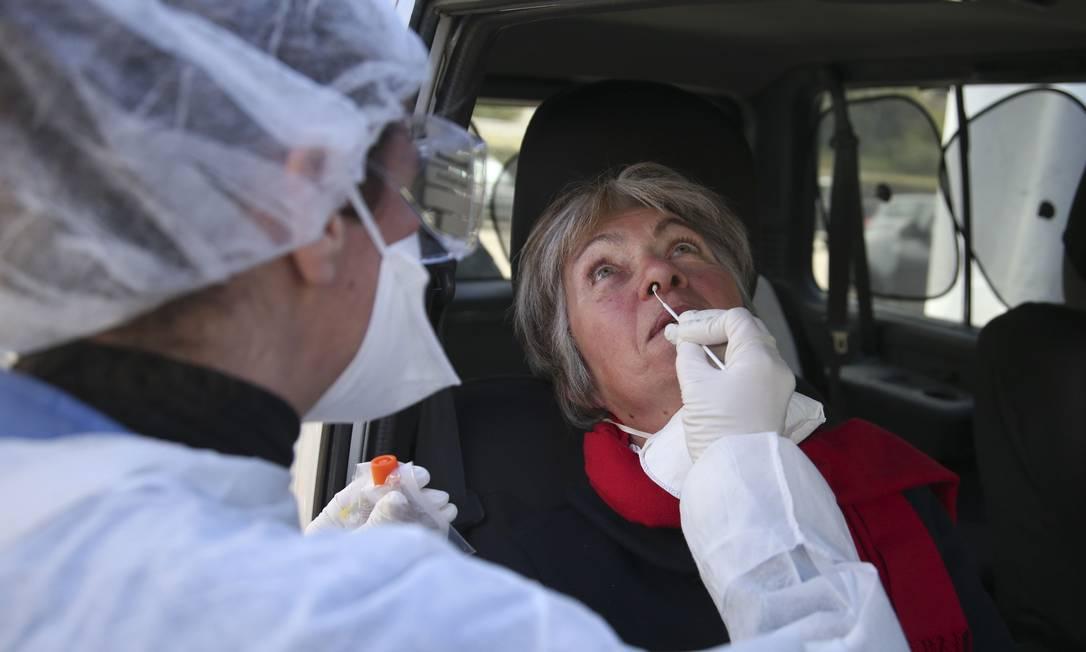 Médico coleta amostra em um centro de testes 'drive-thru' em um paciente em Ajaccio, na ilha mediterrânea francesa da Córsega Foto: Pascal Pcchard-Casabianca / AFP