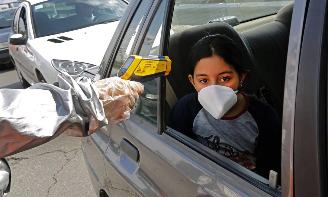 Membros do Crescente Vermelho Iraniano testam pessoas com possíveis sintomas do Covav-19 de coronavírus, em bloqueio na capital Teerã Foto: STR / AFP