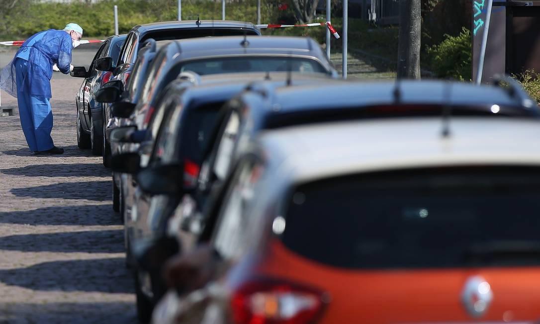 Motoristas fazem fila para passar por teste rápido do novo coronavírus em um estacionamento em Halle, leste da Alemanha. Pesquisadores alemães planejam testar regularmente mais de 100 mil pessoas Foto: Ronny Hartmann / AFP