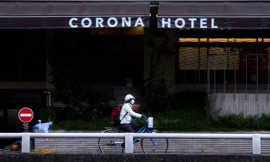 Um ciclista, usando máscar de proteção, passa em frente ao Corona Hotel, em Osaka, no Japão Foto: Edgard Garrido / Reuters